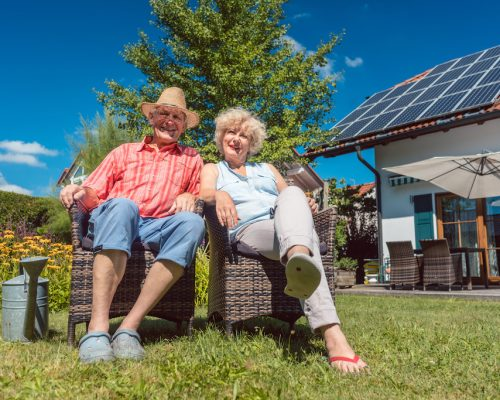 Low-angle view portrait of a happy senior couple in love sitting on chairs while relaxing together in the garden at home in a sunny day of summer